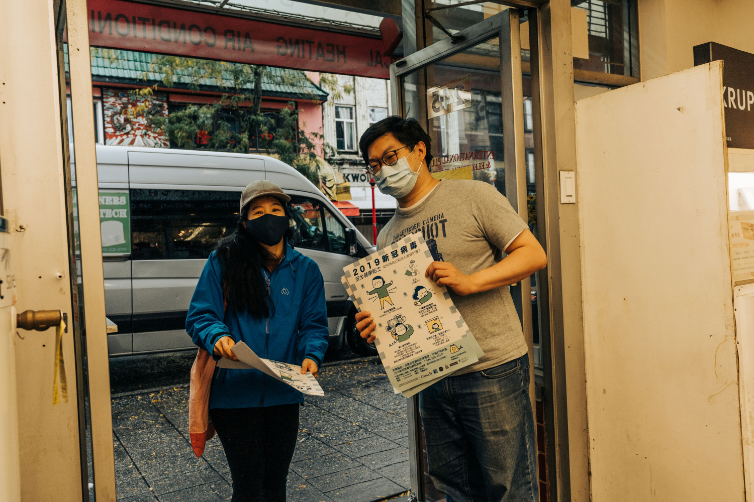 Carmut from hua foundation passes out posters to a business owner in Chinatown.