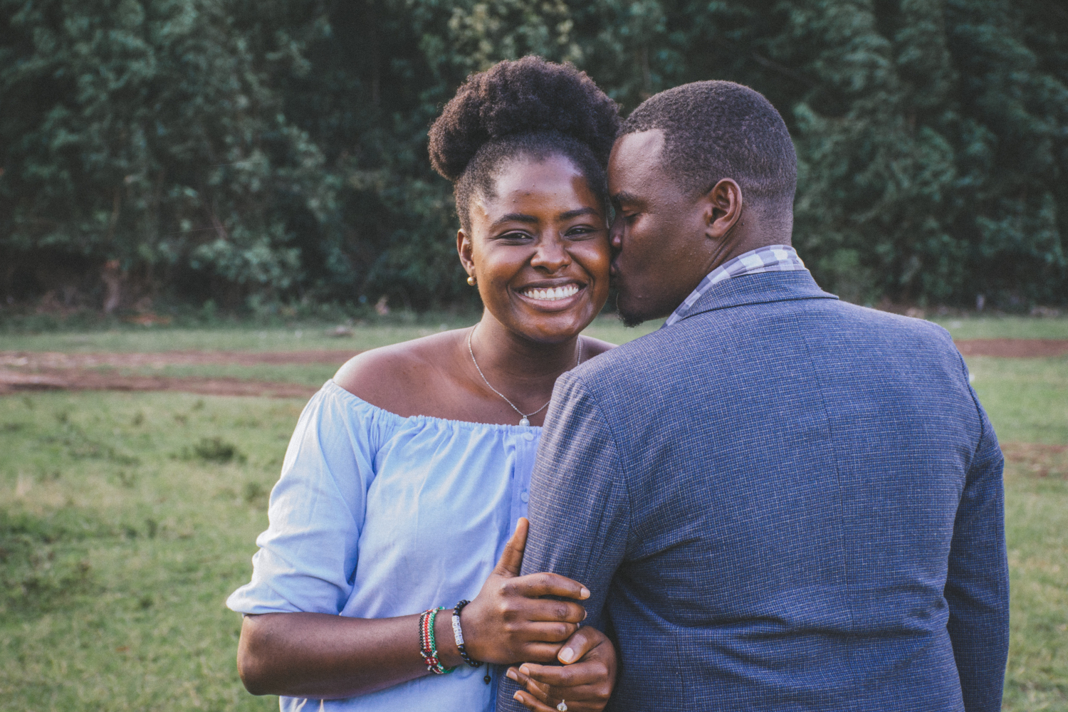 Black couple wearing blue, smiling and being affectionate with each other.