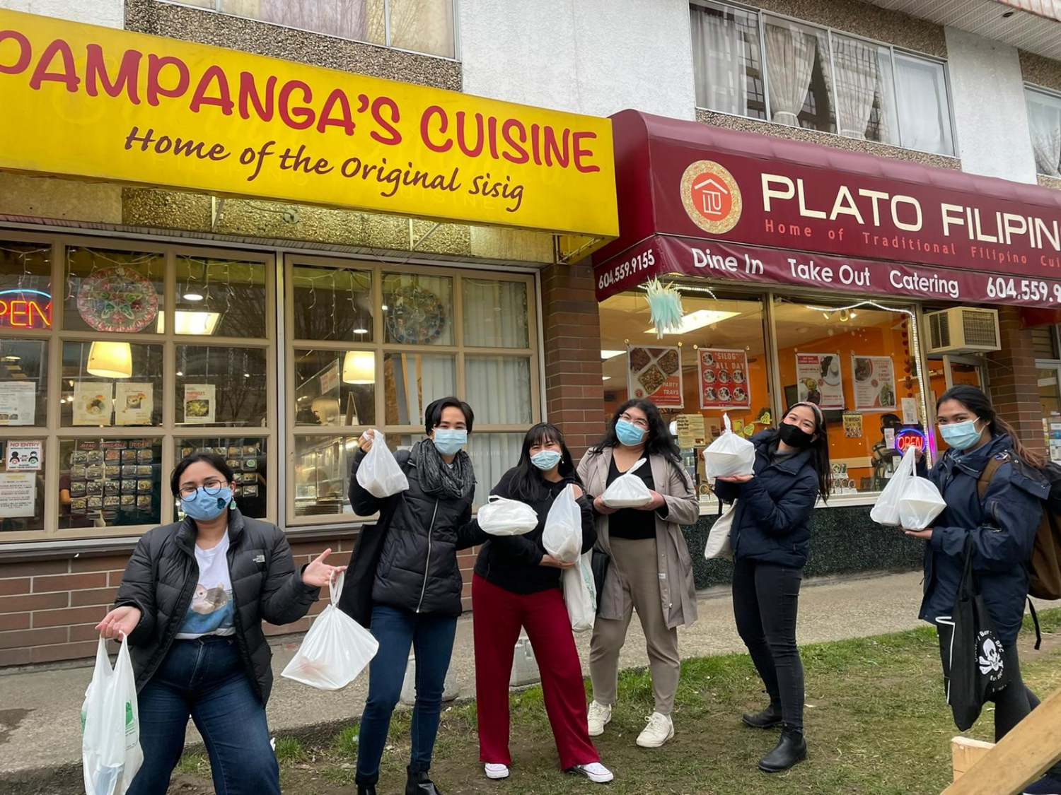 Six young racialized people pose optimistically with bags of takeout in front of Pampanga's Cuisine.