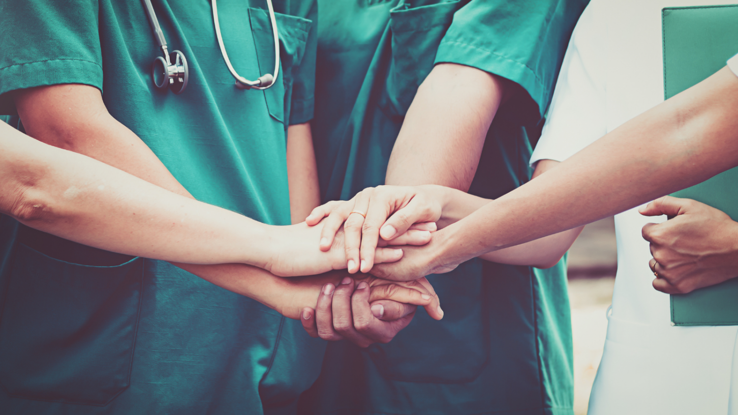 Nurses standing in a circle with hands clasped.