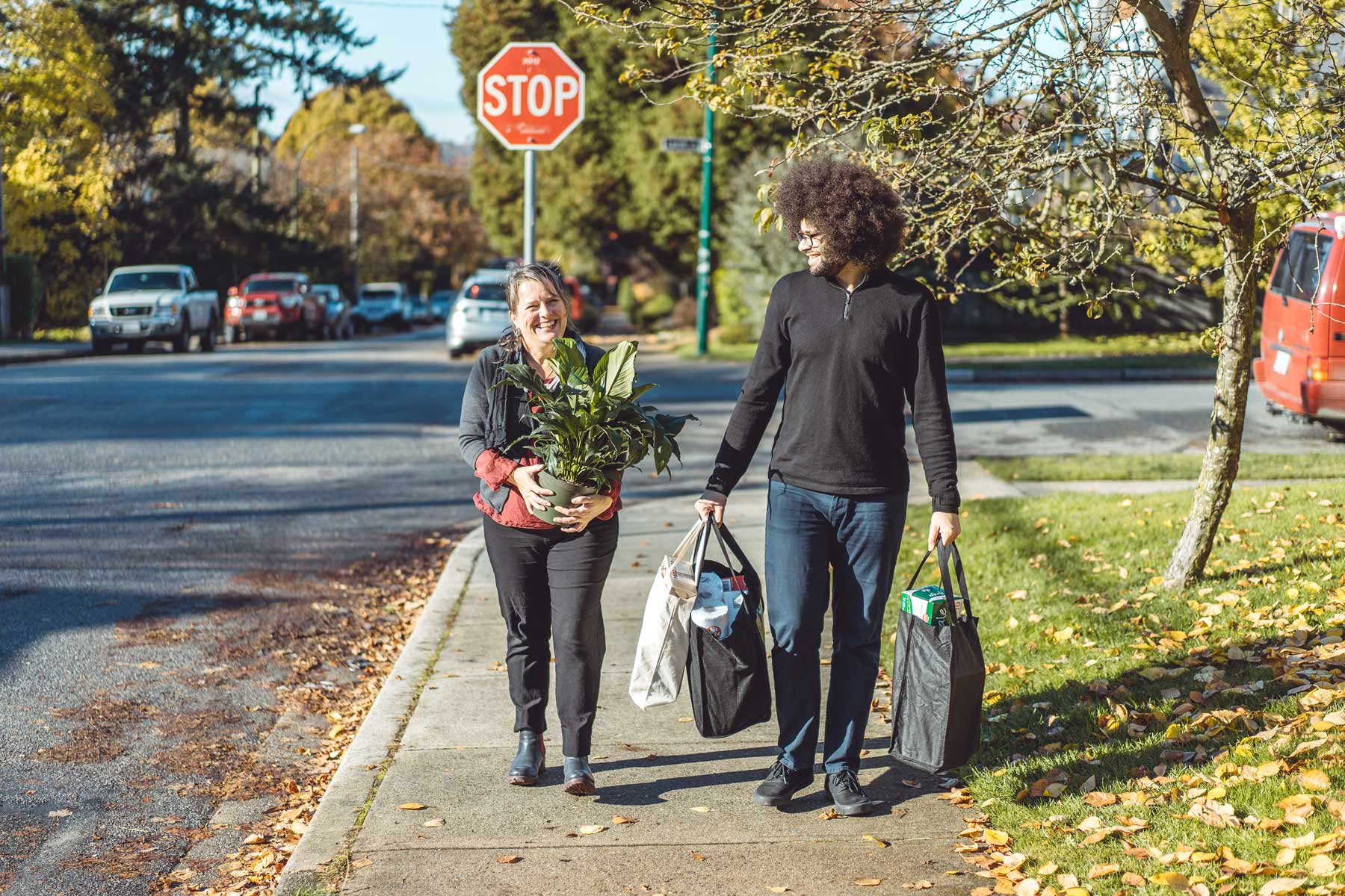 Two people walking on a sidewalk. One is carrying grocery bags, the other is carrying a potted plant.
