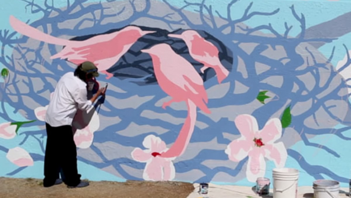 A person painting an outdoor mural depicting a nest with birds and flowers