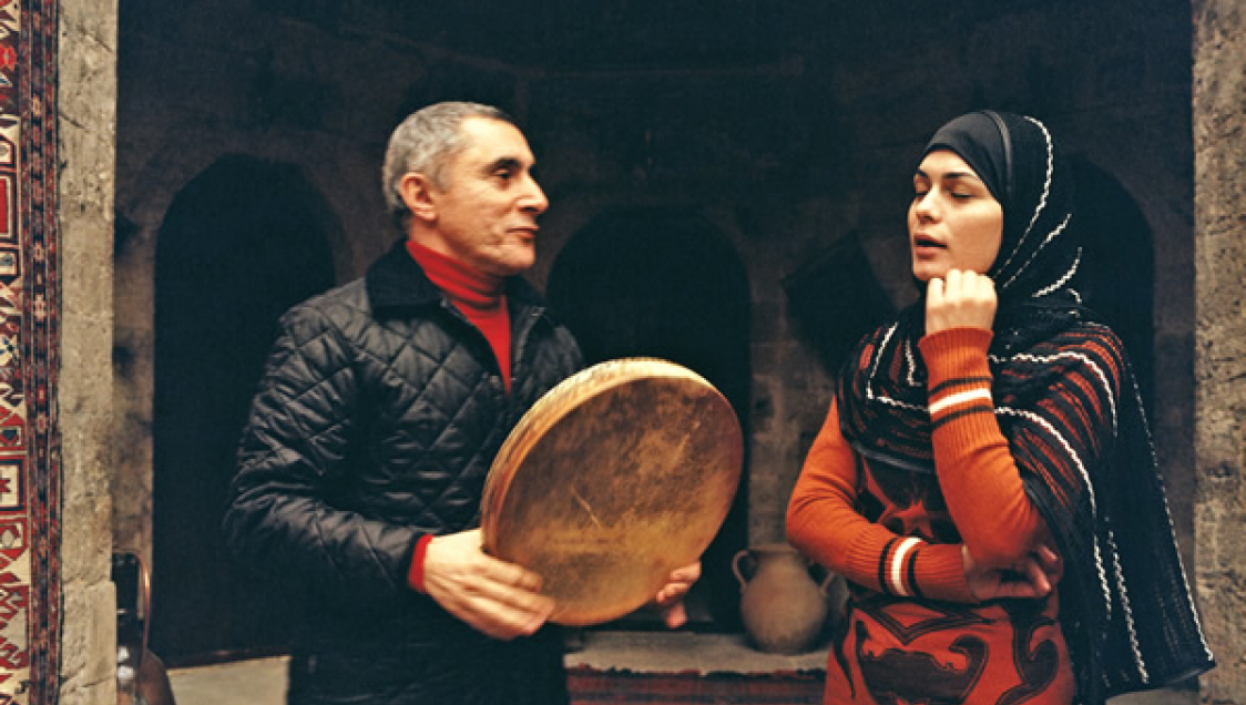 Two people standing in a stone archway, one holding a drum, the other singing