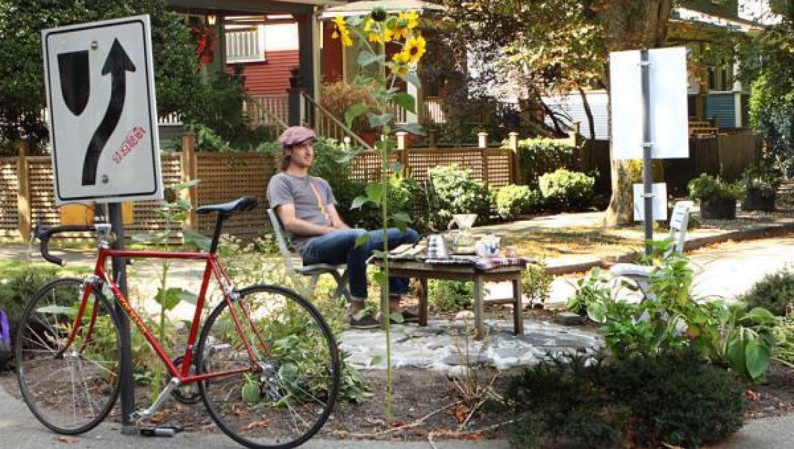 Person sitting in the middle of a roundabout next to a table with refreshments. Flowers and a bicycle are in the foreground.