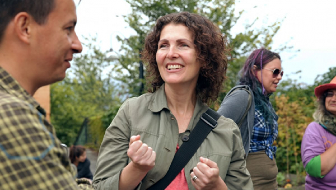 Two adults talking outdoors, with two other adults in the background.