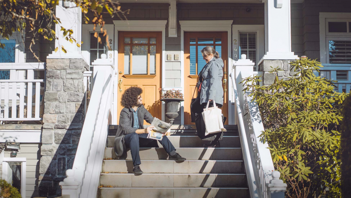 Two people talking on porch steps