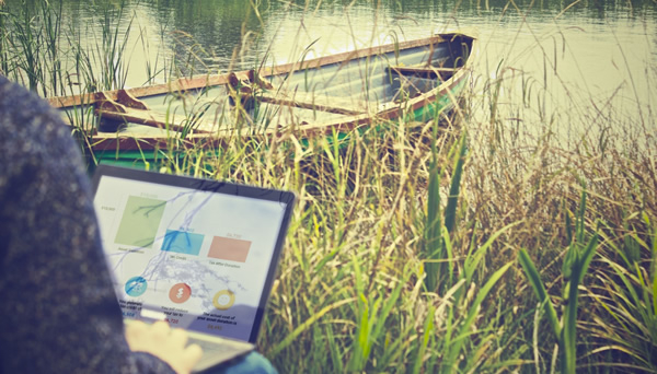Charts on a laptop screen. Laptop user is at the edge of a body of water with grasses and a canoe in the background.