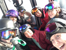 Zero Ceiling youth smiling together while snowboarding