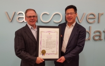 Kevin McCort and Calvin Fong hold Vancouver's Giving Tuesday proclamation.