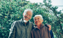 Smiling man and woman standing in front of trees