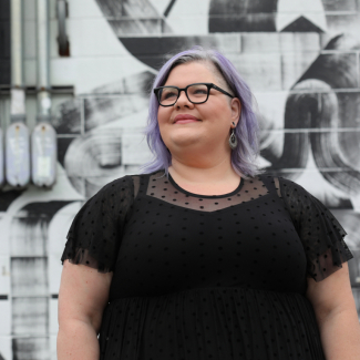 Kait Blake standing in front of a gray mural. She has lavender hair and is wearing a black dress.