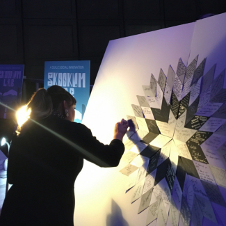 Person piecing together notes onto a canvas to create a Starblanket of stories.